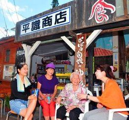 定位置の椅子に座り、近隣の住人らと談笑する平識ツル子さん(右から2人目)=7月30日午後、那覇市牧志の平識商店