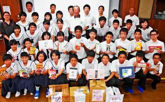 なんじぃフードバンクへ食品を寄贈した南城市立大里中学校2年3組の生徒ら=13日、同校