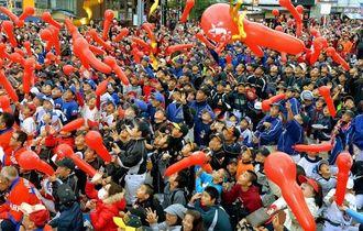 広島カープのセ・リーグ優勝を祝い、赤い風船を飛ばすファン=25日午後、沖縄市・ゲート通り(下地広也撮影)
