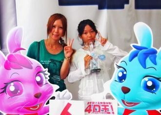 「4D王!」1万人目の入場者の渡久地由紀子さん(左)、桜音さん親子=うるま市・うるまシティプラザ
