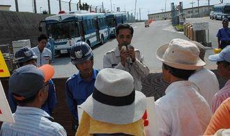 名護防衛事務所の西幸一次長(中央)に石綿工事の説明を求める市民ら=27日午前11時すぎ、キャンプ・シュワブゲート前
