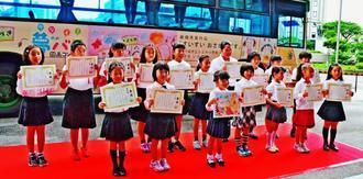 最優秀賞を受賞した佐々木苺さん(前列左から3人目)ら小学生と作品が描かれたバス=25日、県庁