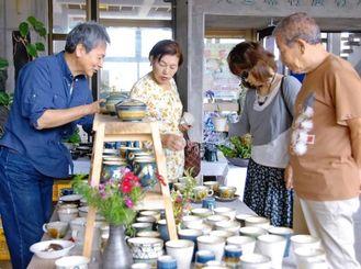 店主の説明を受けながら作品を選ぶ来場客=村農村環境改善センター