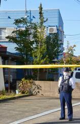 頭のない遺体が見つかった新潟県柏崎市のアパート(奥)=20日