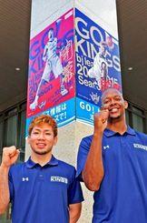 タイムスビルに掲げられたキングスのポスターの前でホーム開幕戦へ向け意気込む岸本隆一選手(左)とアンソニー・マクヘンリー選手=6日、那覇市久茂地