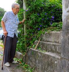 今も残る旧糸満警察署の土台部分を見る金城光栄さん。1935年の写真を見ながら「この上に掲示板があった」と話した=9日、糸満市糸満