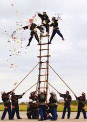 はしごの上部で「火の用心」の垂れ幕を垂らした竹内さん(中央)=10日、市真栄里・石垣市消防本部