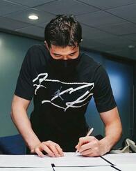 NBAラプターズの公式ツイッターにアップされた書類にサインする渡辺雄太の写真(ラプターズ提供)