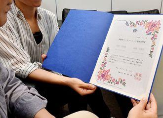 那覇市パートナーシップ登録証明書を手にする2人。「性の多様性を尊重しているところがいいよね」とうなずきあった=那覇市・沖縄タイムス社
