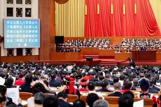 中国全人代の開幕式で、モニターに表示された香港の選挙制度見直しについての議案=5日、北京の人民大会堂(共同)