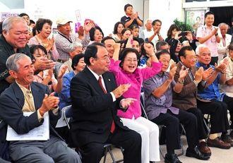 テレビの当選確実の報道にガッツポーズで喜ぶ城間幹子氏(前列左から3人目)と支持者=16日午後8時すぎ、那覇市久茂地の選挙事務所