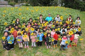保育園の農園で大輪の花を咲かせたヒマワリを一本ずつプレゼントされ、喜ぶ園児たち=豊見城市豊見城