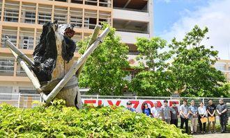 ヘリ墜落現場のモニュメント前で行われた集会=13日午後、宜野湾市・沖縄国際大学ポケットパーク(落合綾子撮影)