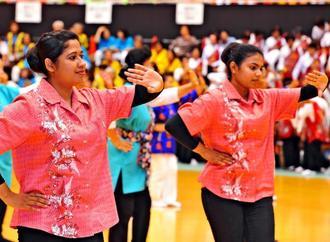 軽快な手踊りを披露するデニカさん(左)とヤムナさん=24日、沖縄市体育館(喜屋武綾菜撮影)