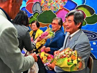 花束を受け取る夜間中学の卒業生=11日、那覇市樋川・珊瑚舎スコーレ