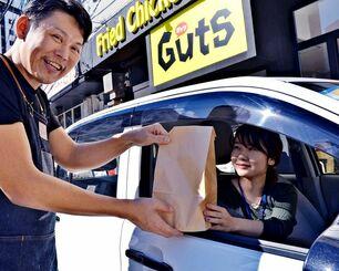 ディキトーンの利用客に商品を渡す木下さん(左)