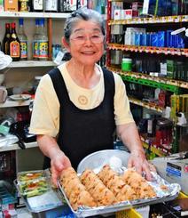 人気メニューのジューシーのおにぎりを手にレジに立つ宮城キク子さん=29日、浦添市屋富祖「宮城商店」