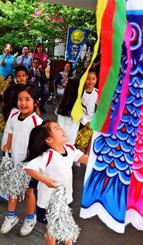 こいのぼり掲揚式でお遊戯を披露する園児ら=19日、宜野湾市役所