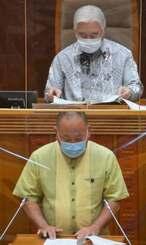 新型コロナウイルス関連で、県議の報酬削減案と、国の予算確保を求める意見書案の提出理由を読み上げた島袋大県議(前)と新里米吉議長=20日、沖縄県議会