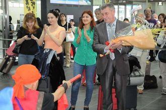 歓迎セレモニーでのエイサーの演舞に拍手を送るロシアからの観光視察団=24日、宮古空港
