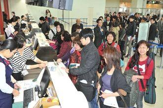 供用が開始した那覇空港国際線ターミナルで、搭乗手続きをする利用客=17日午前