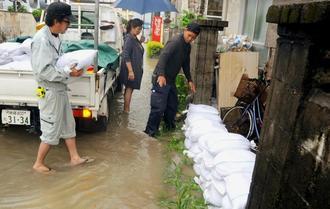 大雨の影響で床下浸水したため土のうを積む住民ら=19日午後2時50分ごろ、豊見城市与根