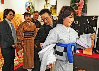 久米島紬の展示即売場では、来場者が着付け体験を楽しんだ=19日、那覇市久茂地・タイムスビル2階ギャラリー