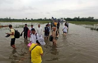 13日、豪雨被害を受けたネパール南部の空港で、水の中を歩く利用者ら(AP=共同)