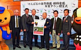6万5千枚余りの年賀状を贈呈する日本郵便の横山邦男社長(中央左)と受け取る宮城久和村長(同右)=13日、国頭村役場