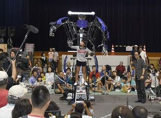 「スケルトニクス・アライブ」ロボットに試乗し、実際に手足を動かす子ども=24日午後、那覇市・県立武道館アリーナ棟