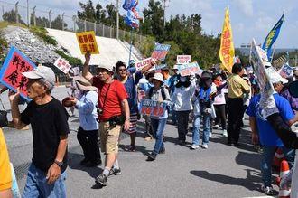 プラカードを掲げデモ行進する参加者=21日、名護市辺野古の米軍キャンプ・シュワブゲート前