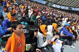 プロ野球のオープン戦が始まり、巨人―広島の試合に見入る観客=21日午後、沖縄セルラースタジアム那覇