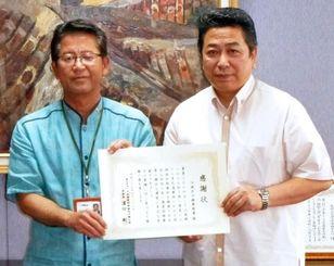 濱田委員長(左)から感謝状を受け取る金城秀実氏