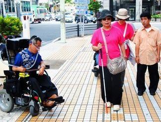 歩道の点字ブロックを確認しながら歩く西玉得奈利子さん(中央)ら。周囲と色の違いが少ないと弱視の人には見えにくいと指摘した=12日午前、那覇市久茂地