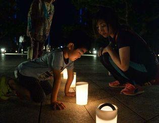 平和祈念公園内にともされたコップキャンドルを見つめる親子連れ=22日、糸満市摩文仁(古謝克公撮影)