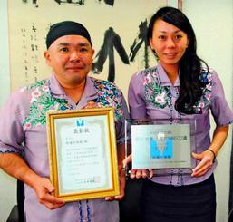 全国2位の表彰状を手に「プロに選んでもらえてうれしい」と喜ぶ澤岻英樹社長(左)と総合企画室の米須明代さん=6日、読谷村宇座・御菓子御殿