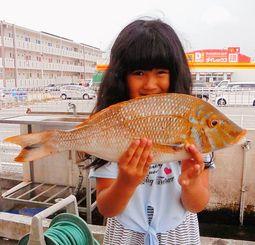 平安座海岸で48.3センチ、1.27キロのタマンを釣った仲本りりさん=7月28日