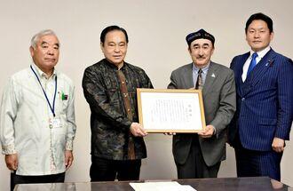 久高友弘議長(左から2人目)に感謝状を贈る日本ウイグル連盟のトゥール・ムハメット会長=23日、那覇市議会
