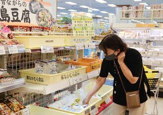 「あちこーこー」の島豆腐を手に取る買い物客=31日、サンエー那覇メインプレイス