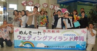空港で歓迎セレモニーを受ける山下雄也さん(前列左から4人目)カップルと清水敬祐さん(前列左から6人目)カップル=22日、那覇空港