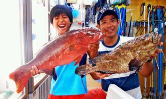 国頭村奥沖合で48センチ、1.7キロのユダヤーミーバイを釣った宮城康弘さん(右)と61センチ、2.94キロのアカジンを釣った當真琉丞さん=7月30日