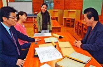 ノートを見て終戦直後をしのぶ赤嶺教頭(左)、元校長の金城さん(右)ら=大宜味村・辺土名高校