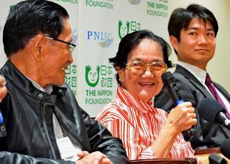 一時帰国会見で、笑顔を見せるフィリピン残留2世の岸本ヤス子さん(中央)、仲地リカルドさん(左)=26日、那覇空港国際線旅客ターミナル(下地広也撮影)