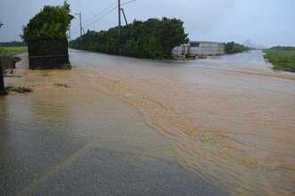 畑から赤土が流れ冠水した道路=16日午前、伊江村