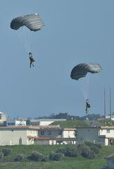 パラシュート訓練で嘉手納基地内に降下する米兵=5月21日午後4時13分、嘉手納町役場屋上から