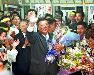 32年ぶりに市政を奪還し、支持者から贈られた花束を手に笑顔の翁長雄志氏(中央)=2000年11月12日、那覇市天久