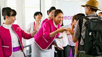 運行を再開した那覇―香港線の搭乗者にシールをプレゼントするピーチ・アビエーションのスタッフ=28日、那覇空港