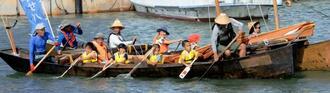 糸満帆掛サバニ振興会の「サバニ体験」を楽しむ久米島の子どもたち=13日、久米島町兼城港