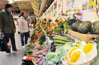 県内各地の特産品を紹介するコーナーを眺める来場者=6日午前、那覇市・県立武道館公園
