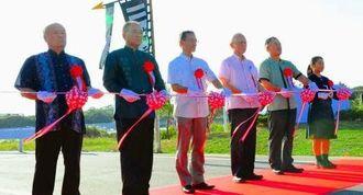 儀間ダムの竣工を祝い、テープカットする県の浦崎副知事(右から3人目)、久米島町の大田町長(同2人目)ら=19日、久米島町・儀間ダム